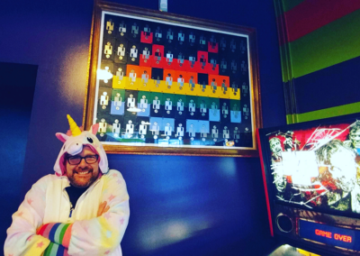 odd man in unicorn costume with space invader floppy disc art
